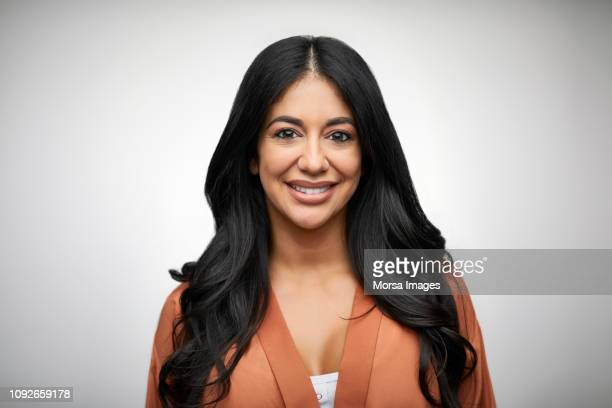 portrait of smiling woman with long black hair - schwarzes haar stock-fotos und bilder
