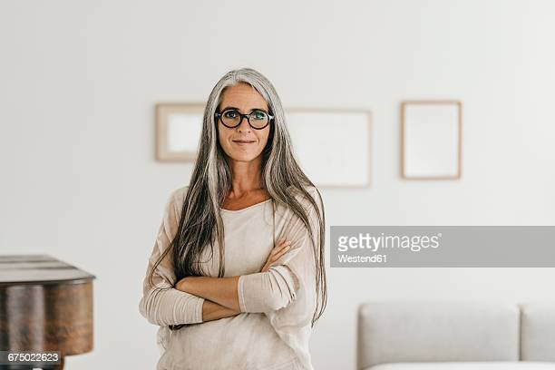 Portrait of smiling woman with long grey hair and spectacles at home