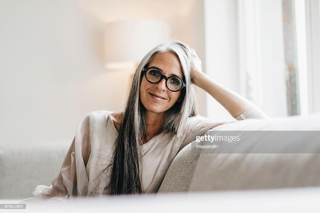 Portrait of smiling woman with long grey hair sitting on the couch : Stockfoto