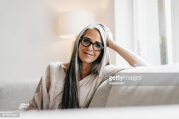 portrait of smiling woman with long grey hair sitting on the couch - frauen über 40 stock-fotos und bilder