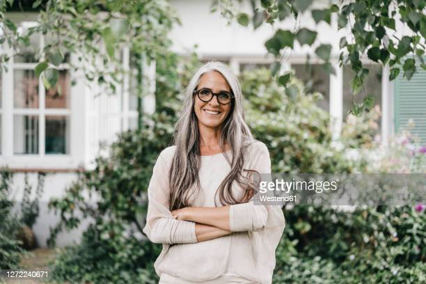 portrait of smiling woman with long grey hair wearing spectacles standing in the garden - 45 49 years stock pictures, royalty-free photos & images