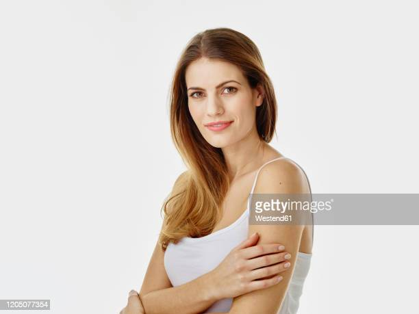 portrait of smiling woman with long hair against white background - spaghetti straps stock pictures, royalty-free photos & images