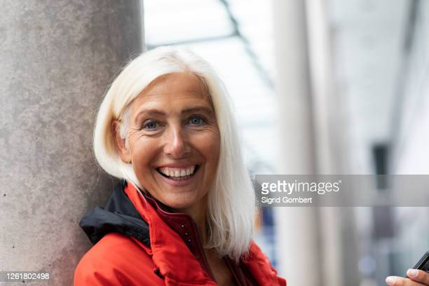 portrait of smiling woman with long white hair, looking at camera. - sigrid gombert stock pictures, royalty-free photos & images