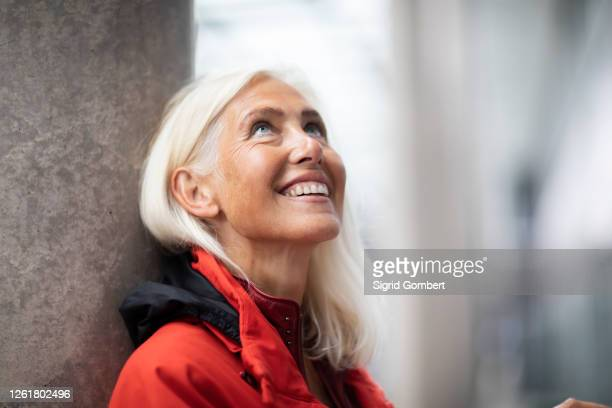 portrait of smiling woman with long white hair, standing outdoors, looking up. - sigrid gombert stock pictures, royalty-free photos & images