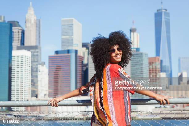 portrait of smiling woman with manhattan skyline - afro amerikaanse etniciteit stockfoto's en -beelden