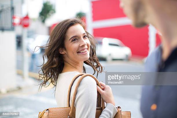 Portrait of smiling woman with meeting a friend on the street