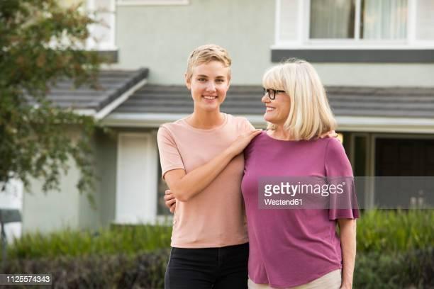 portrait of smiling woman with mother in front of a house - hand auf der schulter stock-fotos und bilder