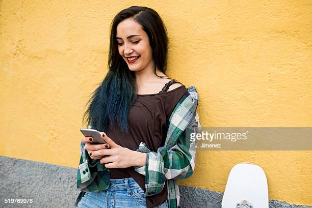 Portrait of smiling woman with on smartphone in front a yellow wall
