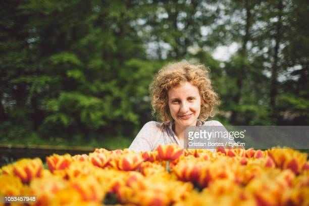 Portrait Of Smiling Woman With Orange Tulips Blooming At Park