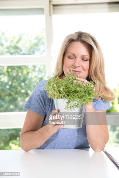 Portrait of smiling woman with pot of herbs in the kitchen
