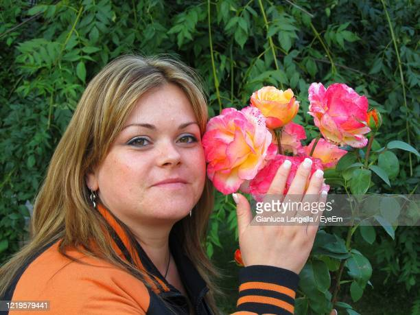 portrait of smiling woman with red flower in sucevita monastery, romania - gianluca langella imagens e fotografias de stock