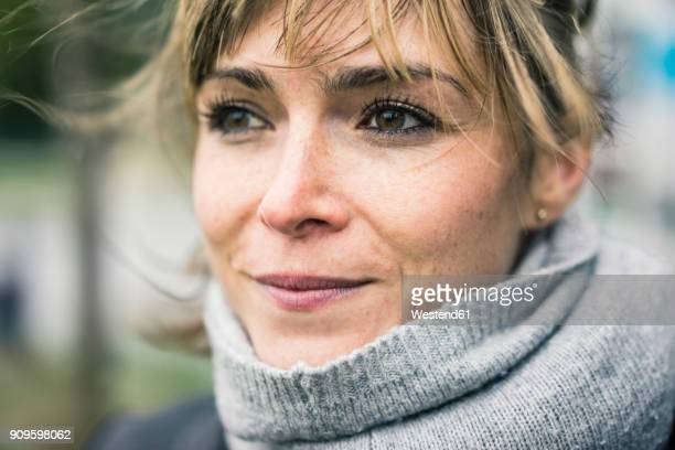 portrait of smiling woman with scarf outdoors - tevreden stockfoto's en -beelden