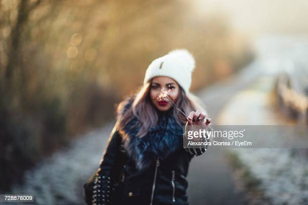 Portrait Of Smiling Woman With Sparklers In Snow