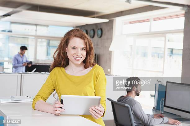 Portrait of smiling woman with tablet computer in the office