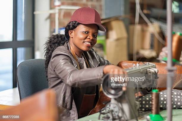 Portrait of smiling woman working at sewing machine in workshop