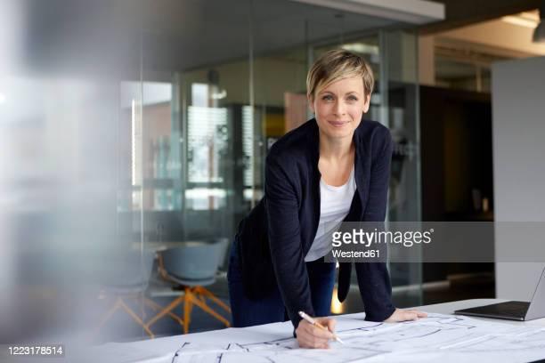 portrait of smiling woman working on construction plan in office - businesswoman stock-fotos und bilder
