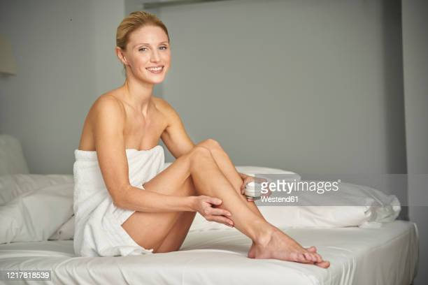 portrait of smiling woman wrapped in a towel sitting on bed applying skin cream on her leg - body care stock pictures, royalty-free photos & images