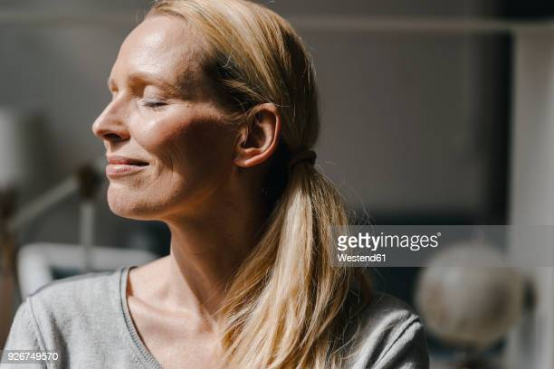 portrait of smiling woman's face in sunlight - zufriedenheit stock-fotos und bilder