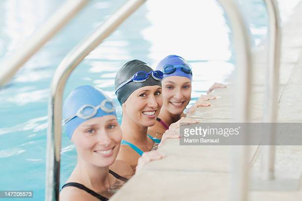 Portrait of smiling women at edge of swimming pool