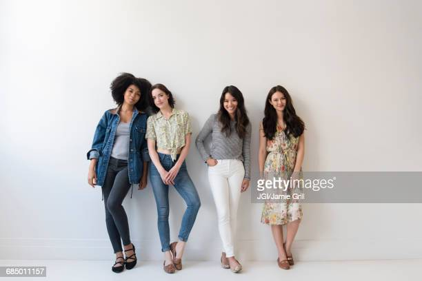 portrait of smiling women leaning on wall - only women stock pictures, royalty-free photos & images