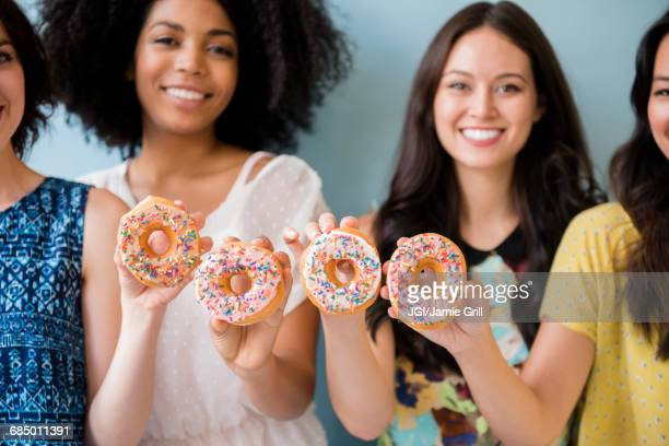 Portrait of smiling women posing with donuts