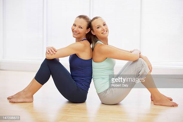 Portrait of smiling women sitting back to back in fitness studio