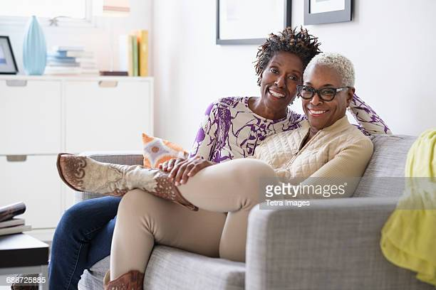 portrait of smiling women sitting in living room - lgbtq  and female domestic life fotografías e imágenes de stock