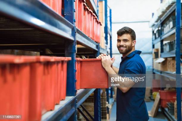 portrait of smiling worker is working in warehouse - polo shirt stock pictures, royalty-free photos & images