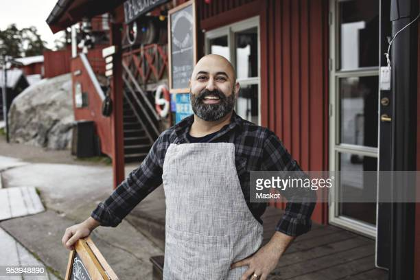portrait of smiling worker standing against factory - artisan stock photos and pictures
