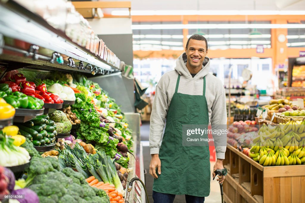 Portrait of smiling worker standing by shelves at supermarket : Stock Photo