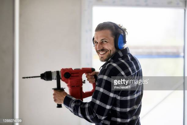 portrait of smiling worker using electric drill on a construction site - drill stock pictures, royalty-free photos & images