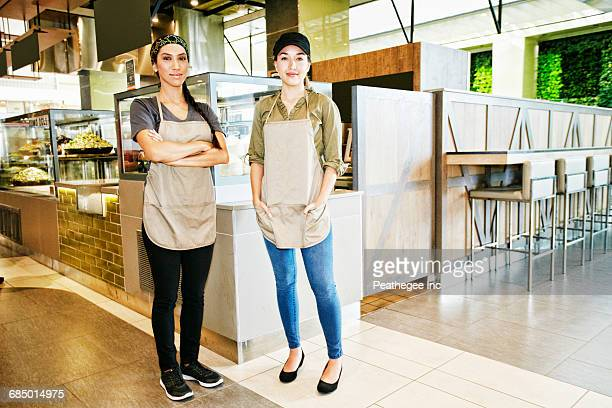 Portrait of smiling workers in food court