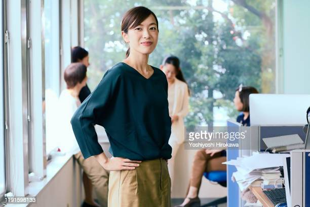 portrait of smiling working business woman and her team - 30代 ストックフォトと画像