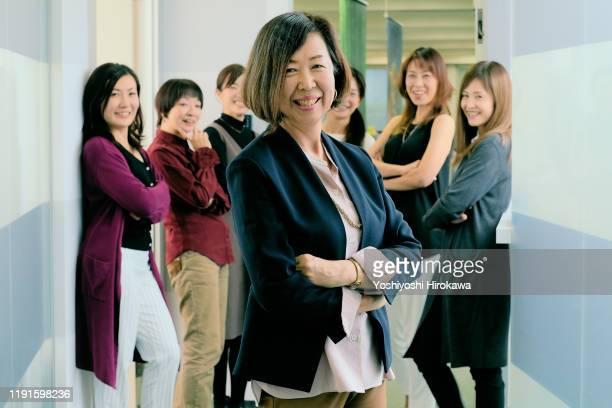 portrait of smiling working senior business woman and her team - directrice stockfoto's en -beelden