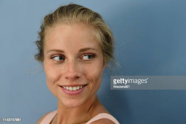 portrait of smiling young blond woman looking sideways - sideways glance stock pictures, royalty-free photos & images