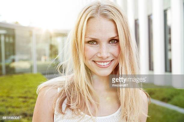Portrait of smiling young blond woman outdoors