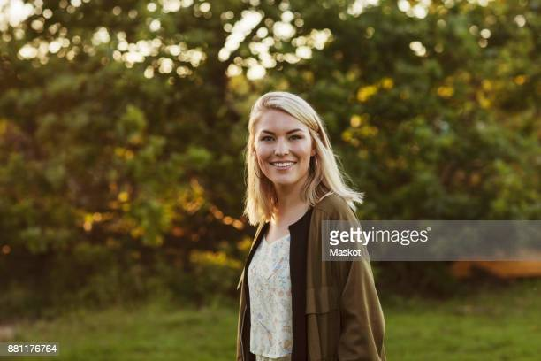 portrait of smiling young blond woman standing against trees - blonde hair stock pictures, royalty-free photos & images