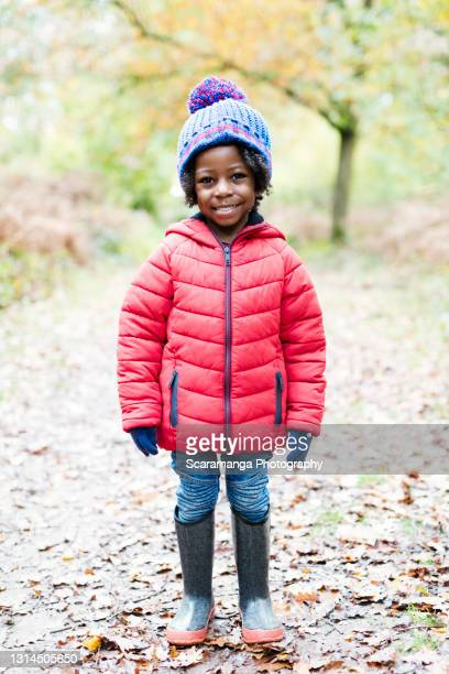 portrait of smiling young boy in forest - coat stock pictures, royalty-free photos & images