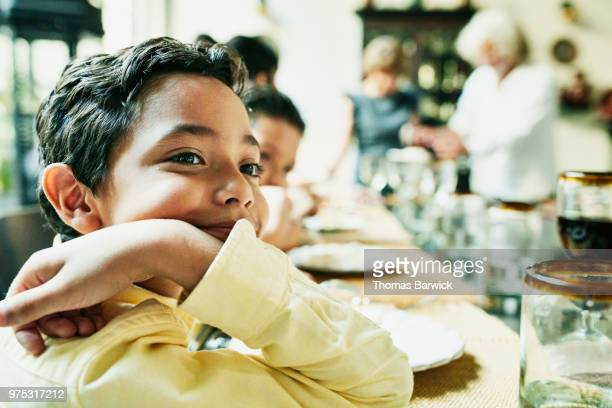 Portrait of smiling young boy sitting at dining room table with family during birthday dinner