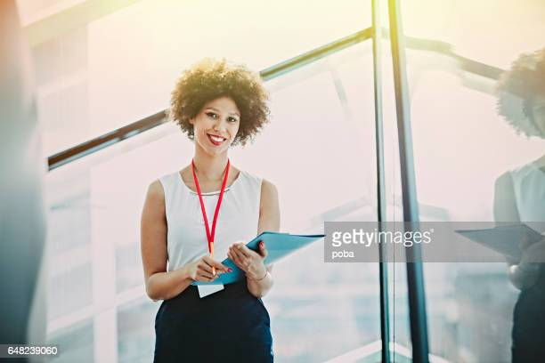 Portrait of smiling young business woman standing in lobby of conference center