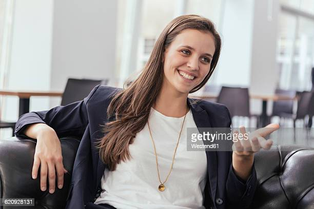 Portrait of smiling young business woman talking to somebody