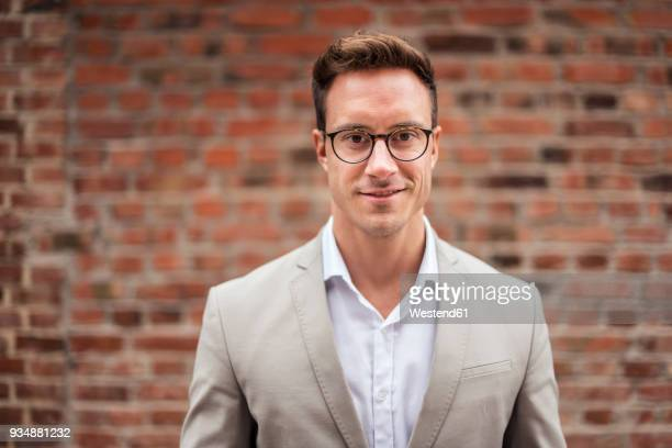 portrait of smiling young businessman at brick wall - blazer jacket stock pictures, royalty-free photos & images