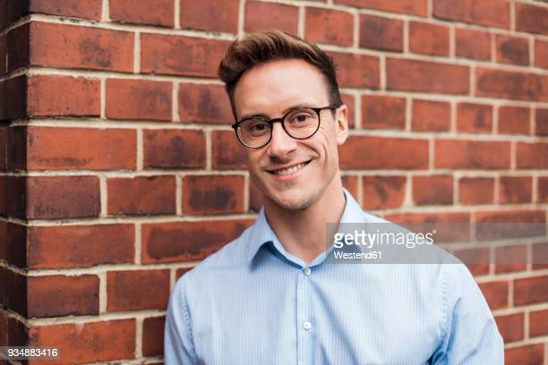 portrait of smiling young businessman at brick wall - alleen één jonge man stockfoto's en -beelden