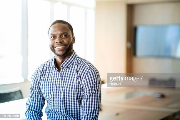 portrait of smiling young businessman at office - black stock pictures, royalty-free photos & images
