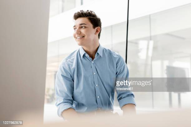 portrait of smiling young businessman at the window in office - one man only stock pictures, royalty-free photos & images