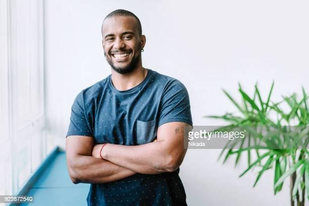 retrato de jovem sorridente empresário no escritório criativo - homens jovens - fotografias e filmes do acervo