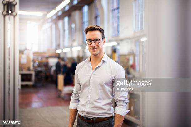 portrait of smiling young businessman in factory - camisa branca - fotografias e filmes do acervo