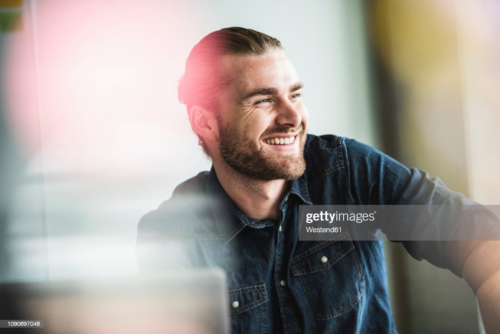 Portrait of smiling young businessman in office : Stock Photo