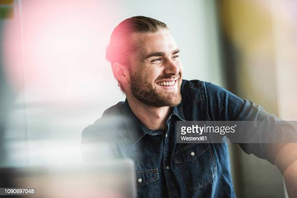 portrait of smiling young businessman in office - lachen stock-fotos und bilder