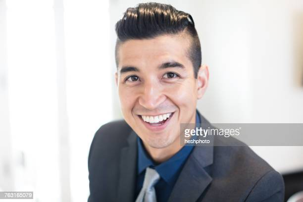 portrait of smiling young businessman in office - heshphoto stock pictures, royalty-free photos & images